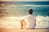Man Traveler sitting on beach seaside looking on sea waves summer vacations Lifestyle concept — Stock Photo