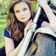 Young beautiful girl sits near the front wheel motorcycle — Stockfoto