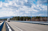 Truck driving on the bridge over the river — Stock Photo