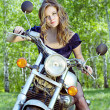 Beautiful young woman sitting on a motorcycle — Stock Photo