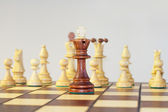 Black King stands in front of the white chess pieces on a chess board — Stock Photo