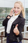Young business woman talking on the phone and shows approving gesture — Stock Photo