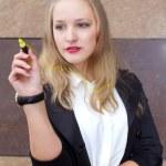 Young beautiful girl writes yellow marker on glass — Stock Photo