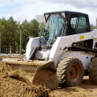 Small bulldozer is gaining ground in the bucket - Stock Photo