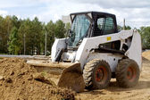 Small bulldozer is gaining ground in the bucket — Stock Photo