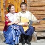 年轻漂亮的女孩和那个坐在一个木房子的门廊上的俄罗斯民族服饰巴拉莱卡的家伙 — 图库照片 #12655561