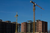 Two tower cranes on the construction of high-rise homes — Stock Photo