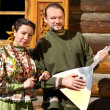 A girl and a young man with balalaika Cossack in national costumes against a wooden house - Stock Photo