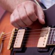 Man's hand, playing the guitar — Stockfoto