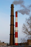Two fuming factory chimneys — Stock Photo