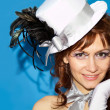 Young sexy girl in a hat and gloves on a blue background — Stok fotoğraf