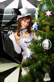 Young beautiful girl in costume Tamer about the Christmas tree decorated — Stock Photo