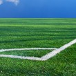 Green artificial turf football and markings near the corner flag - Stock Photo