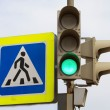 Crosswalk sign and traffic light showing green light for cars — Stock Photo