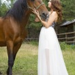 Beautiful girl in a long white skirt with a brown horse — Stock Photo