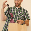 Stock Photo: Surprised young mgets out of paper bag brassiere