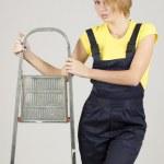 有吸引力的年轻女子,穿上特别保护衣物带梯子站立 — 图库照片