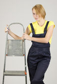 Attractive young woman wearing special protective clothing with ladder stands — Stock Photo