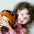 Adorable little girl is hugging big teddy bear — Stock Photo