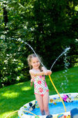 Little girl playing in pool under water splashes — Stock Photo