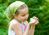 Little girl with chicken outdoors — Stock Photo