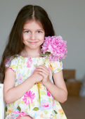 Adorable little girl with peony flower — Stock Photo