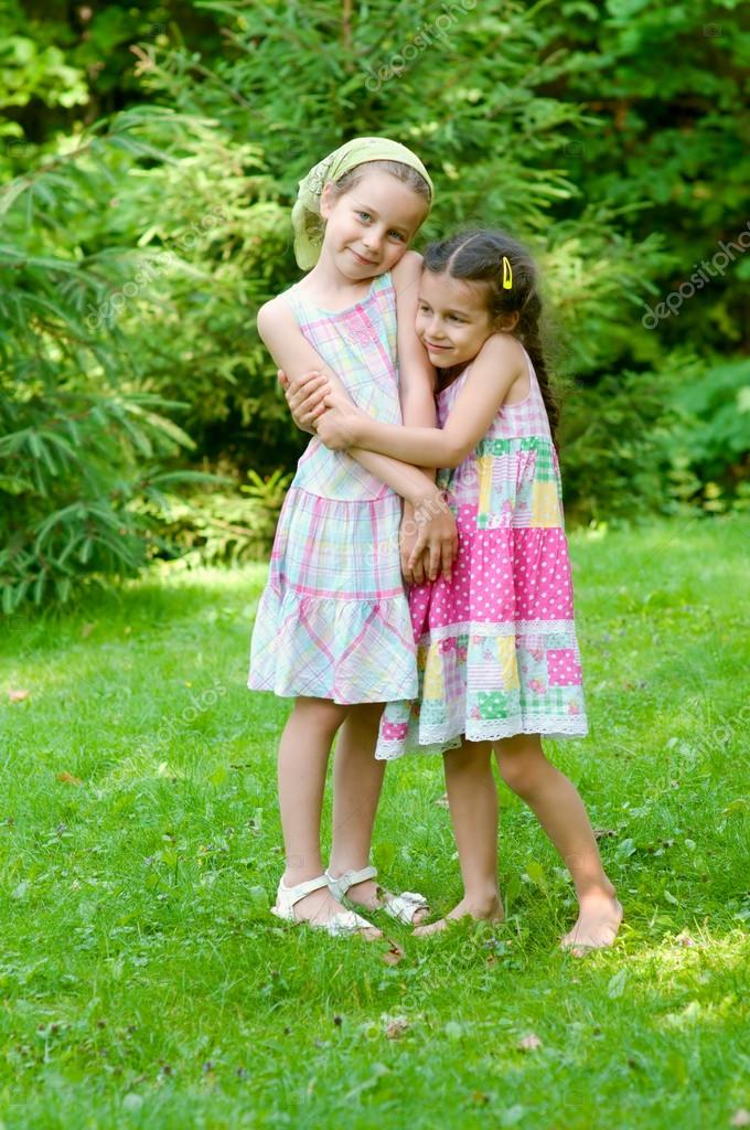 Two adorable little girls standing together in the park  — Stock Photo #12311468