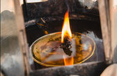 Flames burn in oil burners at buddhist temple — Stock Photo