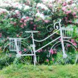 Wrought iron bicycle in garden — Stock Photo