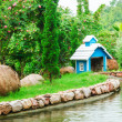 A small wooden house with garden pond — Stock Photo