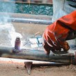 Hand of worker welding steel pole — Stock Photo