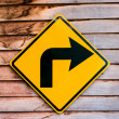Yellow right turning traffic road sign — Stok fotoğraf