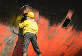 Worker cleaning side of ship at shipyard — Stock Photo
