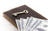 Key and dollar bill on leather wallet — Stock Photo