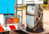 Old dirty gas station pump with fuel truck — Stock Photo