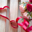 Red satin ribbon heart with artificial rose flowers — Stock Photo