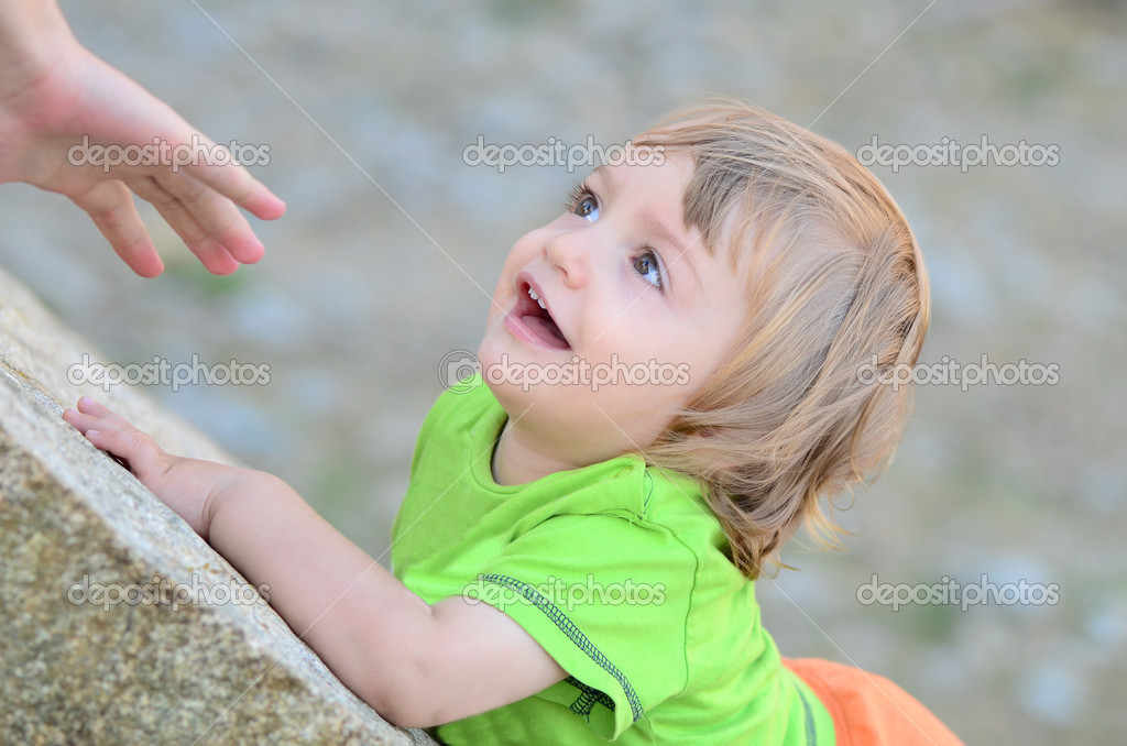 Mother reaches out her baby on a rock — Stock Photo #13546163
