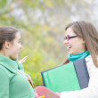 Two Classmates talking in the forest — Stock Photo #16219861