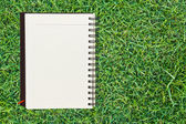 Notebook on grass background — Stock Photo
