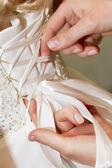 Helping to fast wedding corset. — Stockfoto