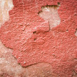 Stock Photo: Red plaster partially peeling off of wall