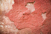 Red plaster partially peeling off of a wall — Stock Photo
