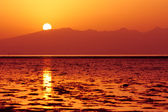 Sun is setting down above sea waters and hills — Stock Photo