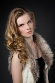 Beautiful blonde woman in fur, dark background — Stock Photo