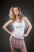 Smiling blonde woman standing in white top — Stock Photo