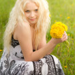 Smiling girl with dandelions, head tilted — Stock Photo #26373675