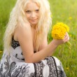 Stock Photo: Smiling girl with dandelions, head tilted