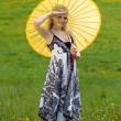Standing girl with parasol on meadow, arm raised. — Stock Photo