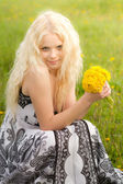 Smiling girl with dandelions, head tilted — Stock Photo