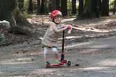 Little girl with scooter in the park — Stockfoto
